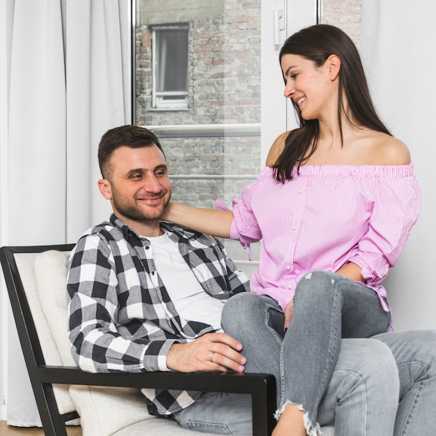 Smiling young woman sitting on her boyfriend's lap sitting on chair Free Photo