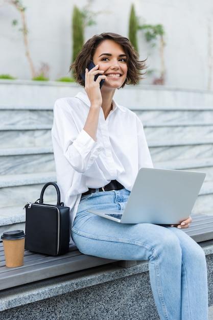 야외 벤치에 앉아 웃는 젊은 여자 프리미엄 사진