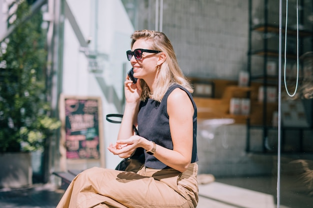 Smiling young woman sitting outside the shop talking on mobile phone Free Photo