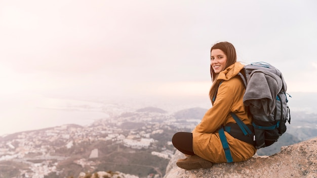 Smiling young woman sitting on the top of mountain with her backpack Free Photo