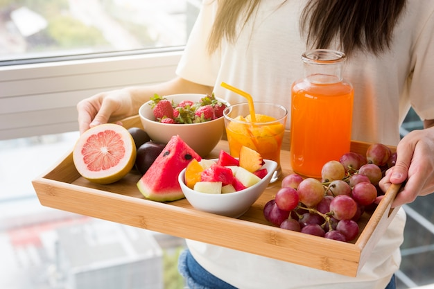 Smiling young woman standing against window holding tray of fruits and juice Free Photo