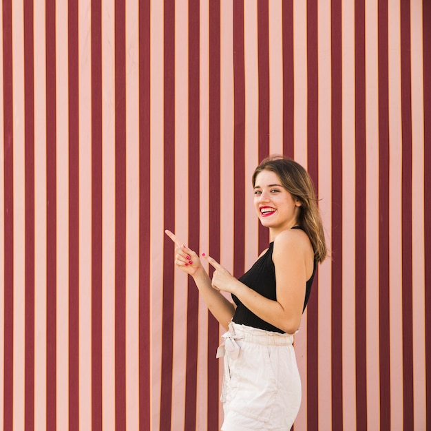 Smiling young woman standing in front of striped backdrop pointing fingers Free Photo