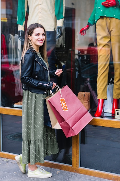 Smiling young woman standing in front of window display holding shopping bags Free Photo