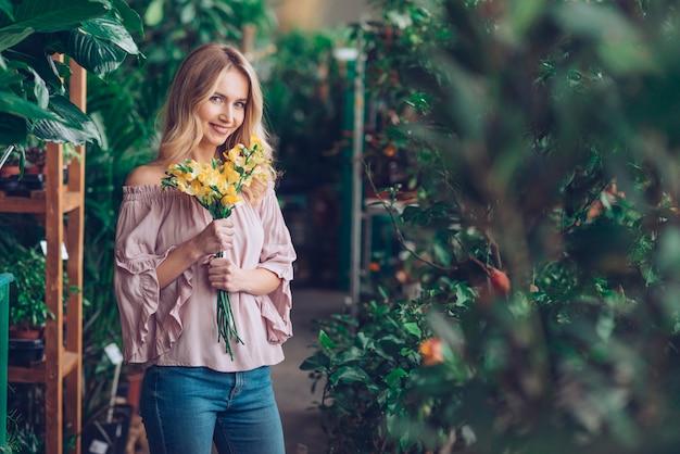 黄色の花の花束を保持している植物保育園に立っている笑顔の若い女性 無料写真