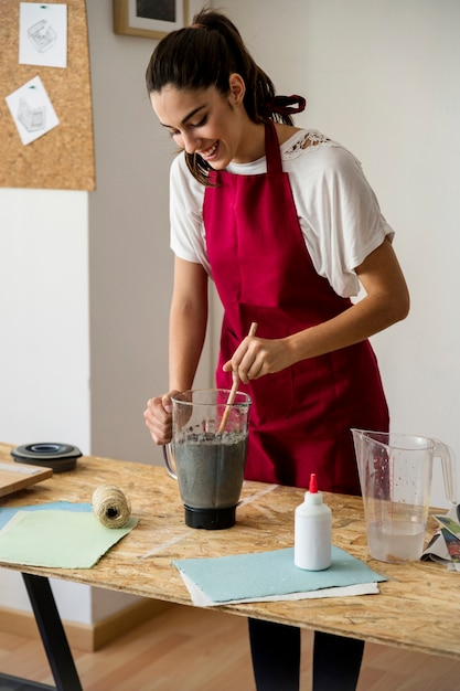 Smiling young woman stirring paper pulp in blender Free Photo