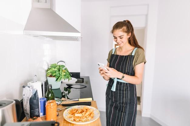 Улыбается молодая женщина, сфотографировать приготовленное блюдо макароны на мобильный телефон Бесплатные Фотографии