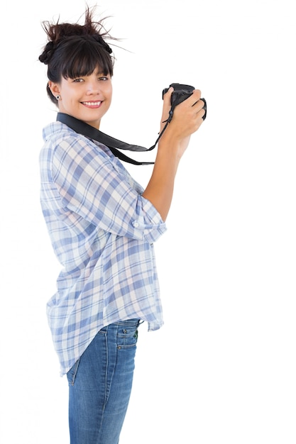 Smiling young woman taking picture with her camera Premium Photo