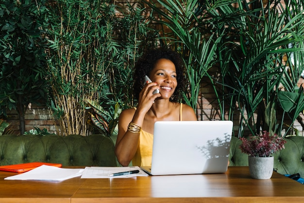 Smiling young woman talking on mobile phone with laptop; documents and pen on wooden table Free Photo