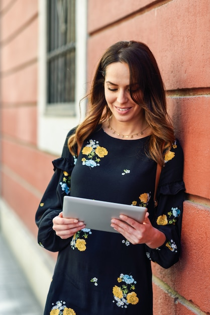 Smiling young woman using digital tablet outdoors. Premium Photo