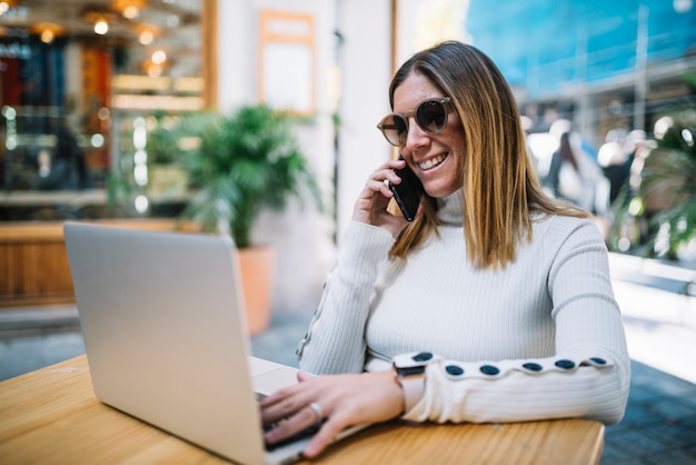 Smiling young woman using laptop and smartphone at table in street cafe Free Photo