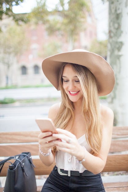 Smiling young woman using smartphone on bench Free Photo