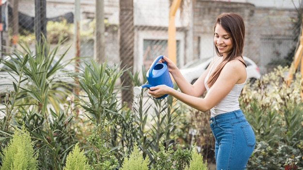 Smiling young woman watering the plant in the greenhouse Free Photo