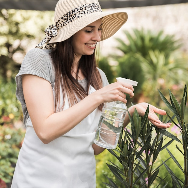 Smiling young woman wearing hat spraying water on green plant Free Photo
