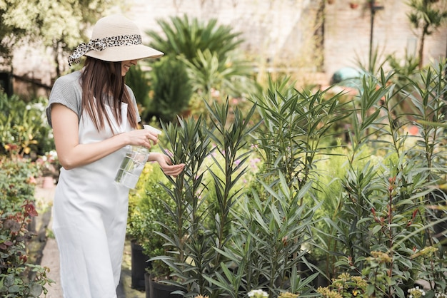 Smiling young woman wearing hat spraying water on green plants Free Photo