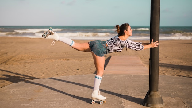Smiling young woman wearing roller skate balancing on one leg at beach Free Photo