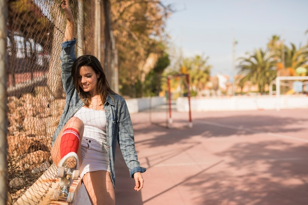 Smiling young woman wearing roller skate sitting near the fence of outdoor court Free Photo