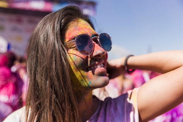 Smiling young woman wearing sunglasses covered with holi colors Free Photo