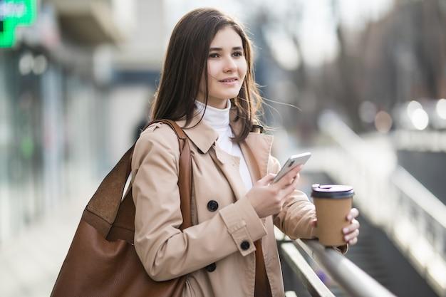 Улыбающаяся молодая женщина с чашкой кофе по телефону в городе Бесплатные Фотографии
