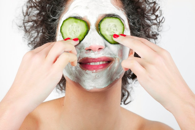 Smiling young woman with face mask putting cucumber slices over her eyes Free Photo