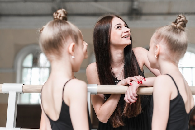 Smiling young woman with her ballerina students in dance class Free Photo