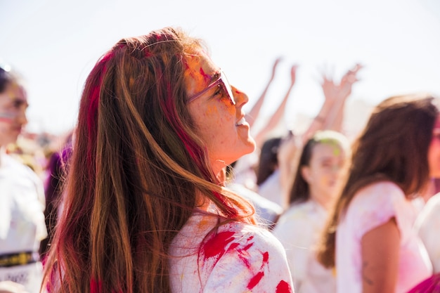 Smiling young woman with holi color looking away Free Photo