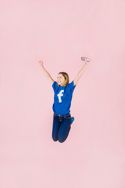 Smiling young woman with smartphone jumping on pink background Free Photo