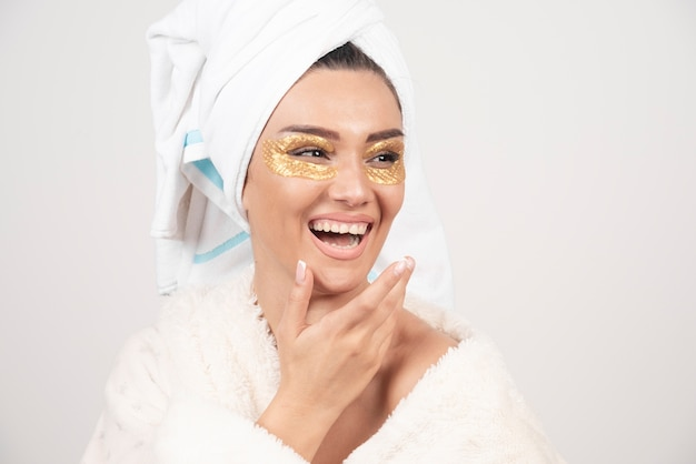 목욕 가운에 눈 아래 패치와 함께 웃는 젊은 여자 무료 사진