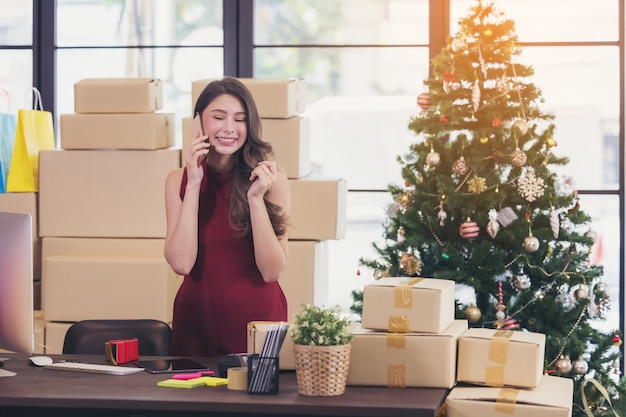 Smiling young woman working from home and talking on smartphone Premium Photo