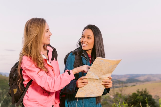 Smiling young women holding map Free Photo