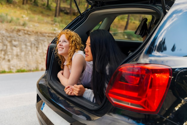 Smiling young women in open car trunk Free Photo