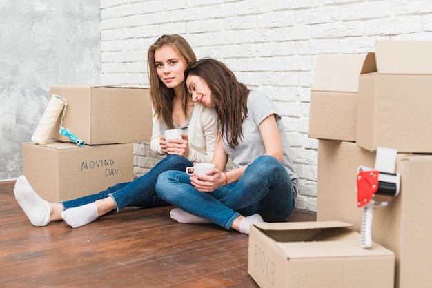 Smiling young women sitting on floor holding coffee cups in hand sitting between the stacked of cardboard boxes Free Photo