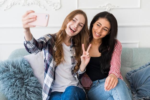 Giovani donne sorridenti che prendono selfie sul telefono Foto Gratuite