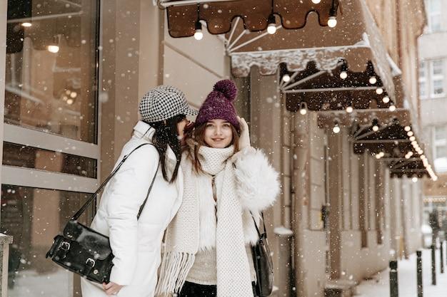 Улыбающиеся молодые женщины в теплой зимней одежде болтают Premium Фотографии