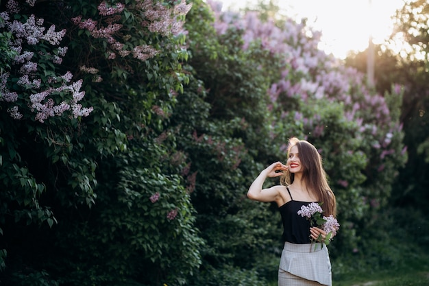 The smilling girl stands near bushes with flowers Free Photo