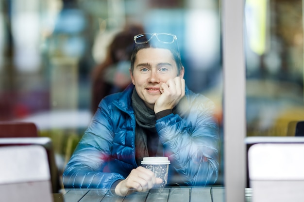 Smilling man with a cup of coffee in a cafe. Premium Photo