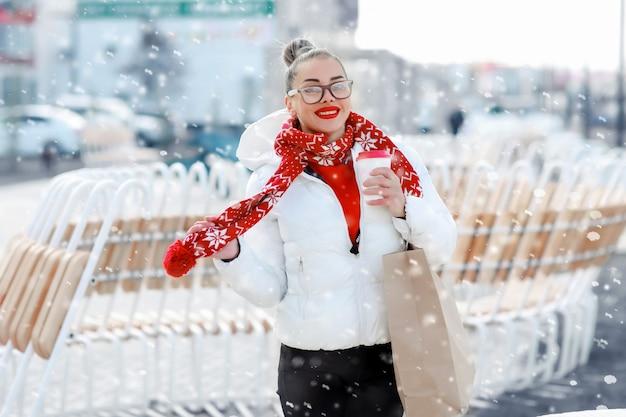 暖かいニットの帽子とミトンのカップを手で保持してsmilling冬の女の子。 Premium写真