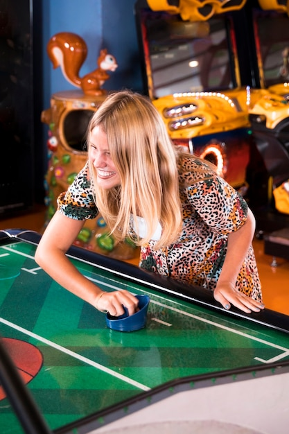 Smilling woman playing air hockey Free Photo