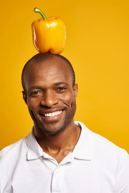Smilling頭の上に黄色のピーマンとアフリカ人。 Premium写真
