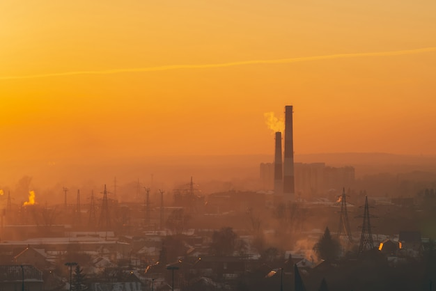 Smog among silhouettes of buildings on sunrise. smokestack in dawn sky. environmental pollution on sunset. harmful fumes from stack above city. mist urban background with warm orange yellow sky. Premium Photo
