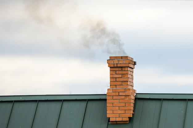 Дым из трубы, отопление. вздымающийся дым. выходит из дымохода дома на фоне голубого неба Premium Фотографии
