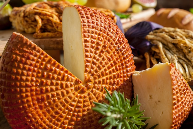 Smoked cheese pigtail, traditional polish smoked cheese, chechil cheese on the wood background. Premium Photo