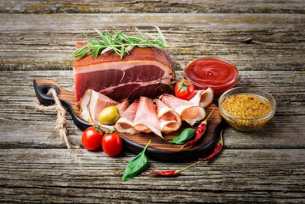 Копченая ветчина на деревянном столе с розмарином, перцем и помидорами черри. Premium Фотографии
