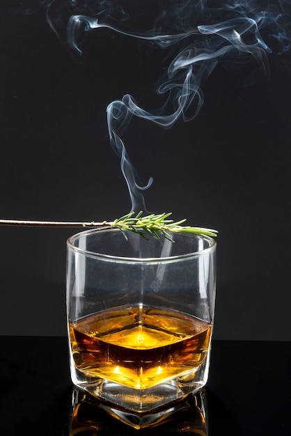 Smoked rosemary on whisky glass Free Photo