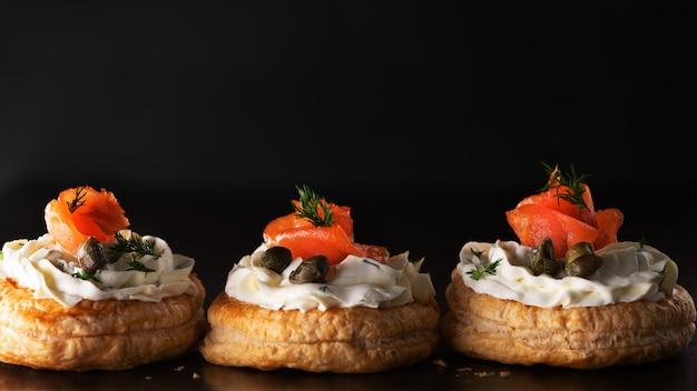 暗いバナーのクリームチーズとスモークサーモンのタルトスナック Premium写真