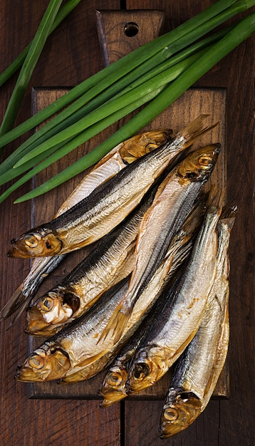 Smoked sprat and green onion  on a cutting board. smoked fish. top view Free Photo