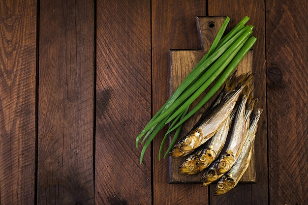 Smoked sprat and green onion  on a cutting board on a wooden background. smoked fish. top view Premium Photo