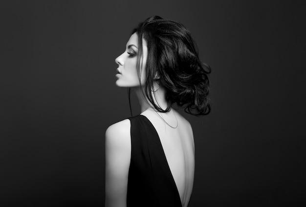 Классический макияж smokey на лице женщины, красивые большие глаза. мода идеальный макияж, выразительные глаза на лице женщины, гладкие черные брови, облизанные волосы брюнетки. портрет женщины на темной стене Premium Фотографии