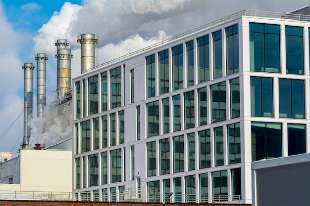 Smoking factory pipes and office building of the factory Premium Photo
