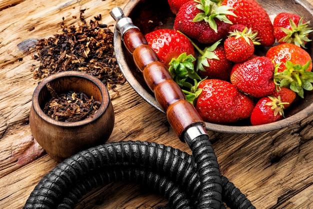 Smoking hookah on strawberry Premium Photo