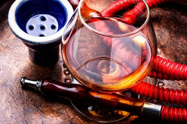 Smoking hookah with cognac flavor Premium Photo